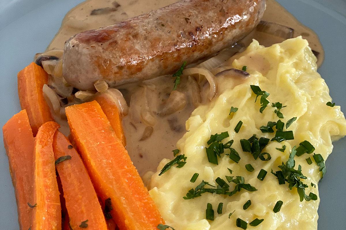 Grobe Bratwurst mit Zwiebelsauce und Karotten